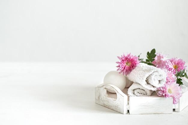 Composition de spa avec des produits de soins corporels et des fleurs sur un espace de copie de fond clair.