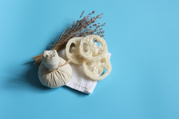 Composition de spa avec sac à base de plantes, luffa et lavande sur fond bleu.