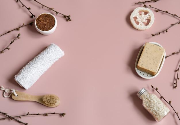 Composition de spa avec savon, brosse, luffa, sel de mer et serviette parmi les branches d'arbres printaniers vue de dessus.