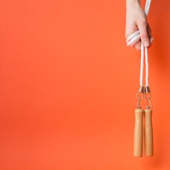 Composition de sport moderne avec la main tenant la corde à sauter