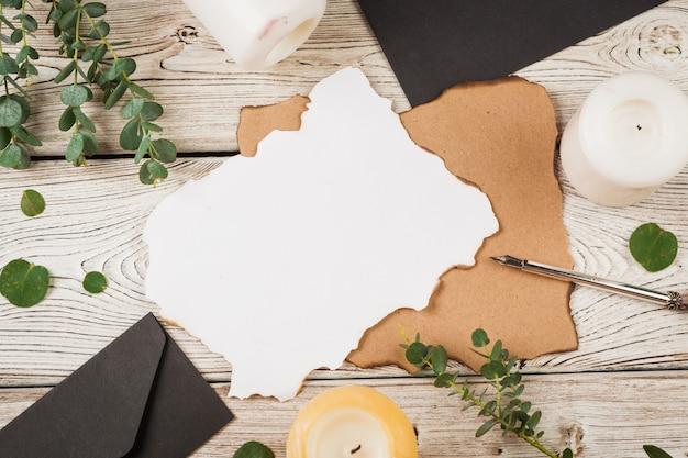 Composition de style vintage avec du papier patiné et une plume sur la table en bois se bouchent