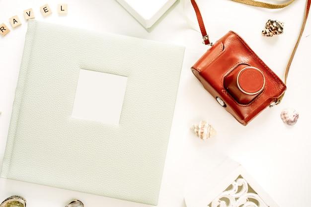 Composition de style voyage avec album photo, appareil photo rétro, sculpture d'oiseau sur une surface blanche. mise à plat, vue de dessus