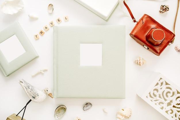 Composition de style voyage avec album photo, appareil photo rétro, sculpture d'oiseau sur une surface blanche