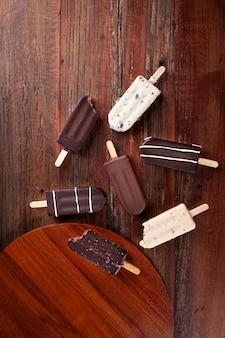 Composition avec des sucettes glacées au chocolat sur fond en bois. vue de dessus