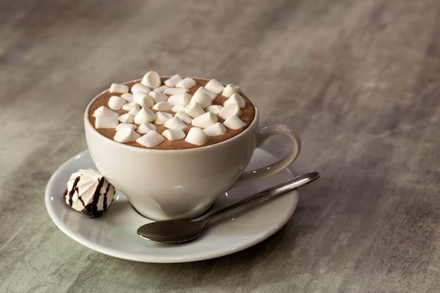 Composition de tasse de café avec des guimauves sur une assiette en porcelaine sur fond clair, vue de dessus.
