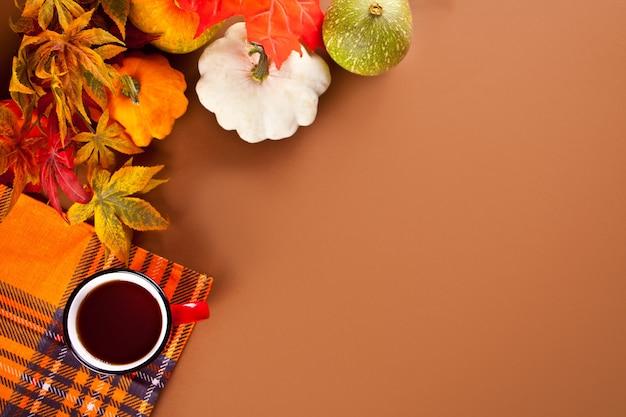 Composition avec une tasse rouge avec du thé, des feuilles d'automne et de petites citrouilles sur le fond des muscles. récolte d'automne. notion d'automne.