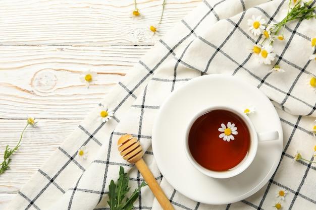 Composition avec tasse de thé à la camomille sur bois blanc