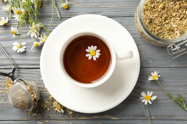Composition avec tasse de thé à la camomille sur fond de bois blanc