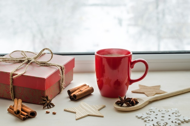 Composition de temps de noël avec tasse rouge et cadeau sur le rebord de la fenêtre
