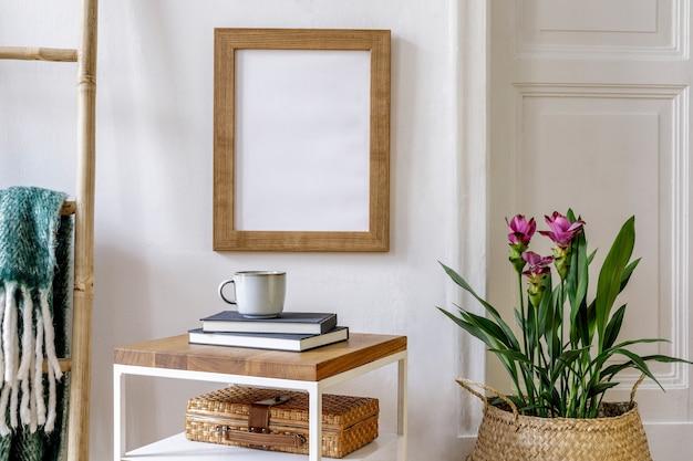 Composition tendance de l'intérieur du jardin avec cadre d'affiche, table basse en bois, plantes de curcuma, décoration, plaid, livre, accessoires personnels dans un décor élégant.
