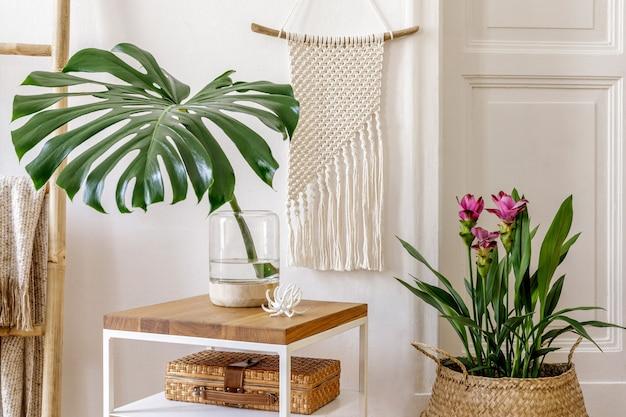 Composition tendance de l'intérieur du jardin avec table basse en bois, plantes et fleurs, échelle, décoration en rotin, macramé, accessoires personnels, mur blanc dans une décoration élégante.