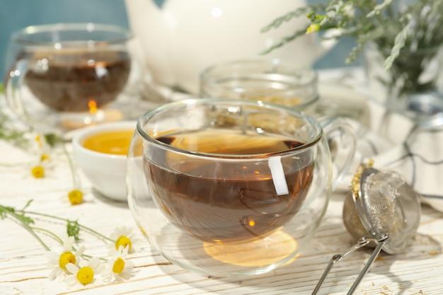 Composition avec thé à la camomille sur table en bois blanc