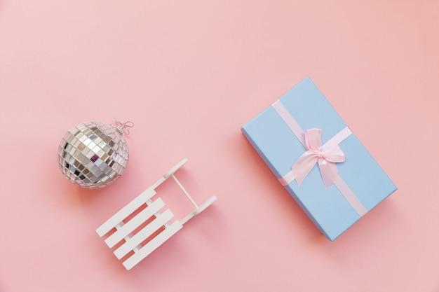 Composition tout simplement minimale objets d'hiver ornement balle traîneau boîte cadeau isolé sur pastel rose