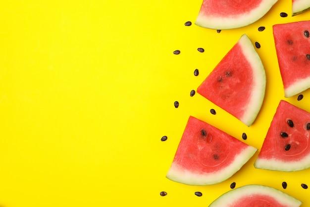 Composition avec des tranches de melon d'eau sur l'espace jaune, vue de dessus