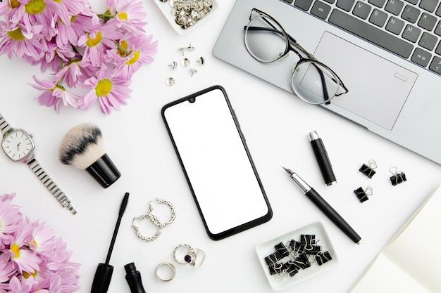 Composition de travail sur fond blanc avec différents appareils et objets