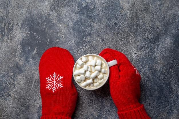 Composition de vacances confortable de noël et du nouvel an avec écharpe, femme mains en mitaines, tasses avec boisson chaude et guimauve sur le fond de béton gris. mise à plat, vue de dessus.