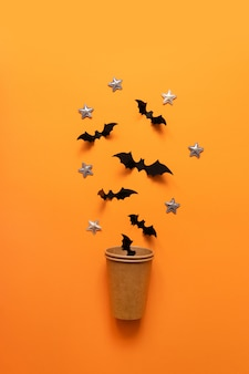 Composition de vacances halloween des chauves-souris noires volent hors de gobelet en papier sur la surface orange.