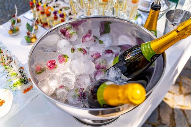 Composition de vacances de luxe. une bouteille de champagne frais dans un seau à glace et des verres vintage. table de fête en arrière-plan.