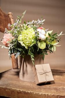 Composition de vacances moderne écologique avec bouquet de fleurs dans un vase en carton bricolage debout sur une vieille chaise en bois et boîte-cadeau bricolage sur fond beige. style hygge. orientation verticale.