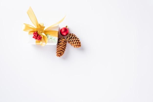 Composition de vacances de noël avec une boîte-cadeau et un ruban d'or, des branches de sapin, des pommes de pin