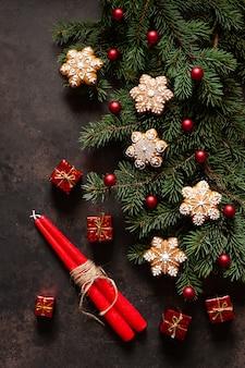 Composition de vacances de noël avec des branches de sapin, des cônes, du pain d'épice, un décor de noël et deux bougies rouges
