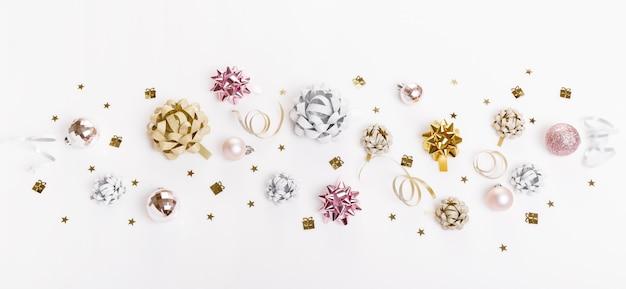 Composition de vacances de noël. motif festif créatif en argent doré, boule de vacances décor rose de noël avec ruban, flocons de neige sur fond blanc. mise à plat, vue de dessus