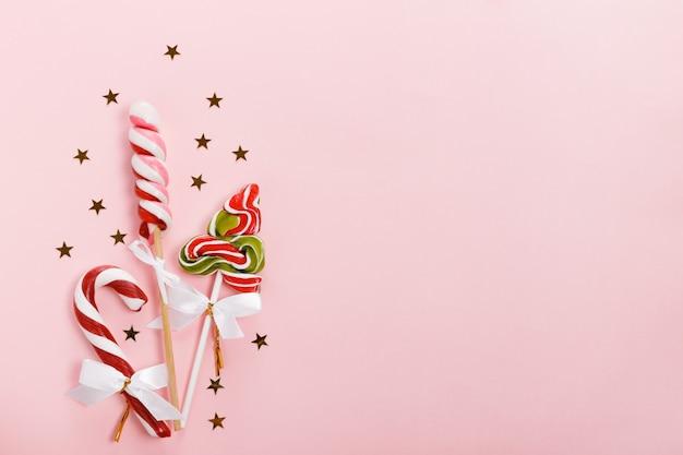 Composition de vacances de noël, motif. motif festif en argent doré, décor rose de noël, canne en bonbon de noël avec ruban, flocons de neige sur fond rose. mise à plat, vue de dessus