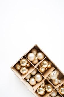 Composition de vacances de noël nouvel an. boules de boules de noël dorées sur blanc. concept festif plat lapointe, vue de dessus.