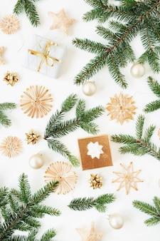 Composition de vacances de noël nouvel an. branches de sapin, coffrets cadeaux, boules de noël, décorations en paille sur blanc