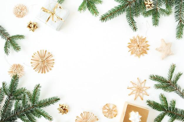 Composition de vacances de noël nouvel an. cadre avec copie espace de branches de sapin, coffrets cadeaux, décorations en paille sur blanc
