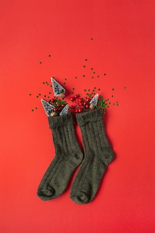 Composition de vacances de noël nouvel an. chaussettes décorées de sapins jouets, de baies et de confettis sur fond rouge