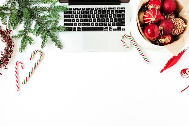 Composition de vacances de noël nouvel an. espace de travail de bureau à domicile avec ordinateur portable, boules de noël, branches de sapin, bâtonnets de bonbons sur blanc