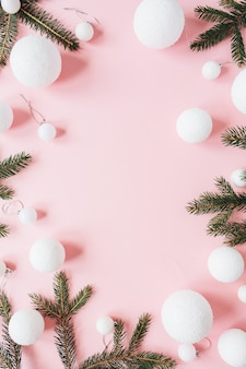 Composition de vacances de noël nouvel an. maquette de cadre avec espace copie vierge, branches d'aiguille de sapin, boules de noël sur rose