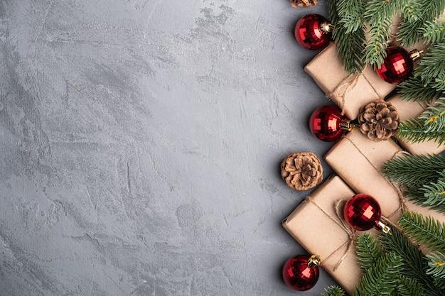 Composition de vacances de noël. ornement rouge et décorations de babiole, sapin, cadeaux et pommes de pin. copier l'espace