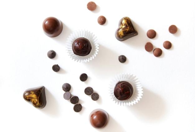 Composition avec une variété de truffes au chocolat faites à la main de luxe, avec de beaux ornements et des tablettes de chocolat dispersées sur une surface blanche