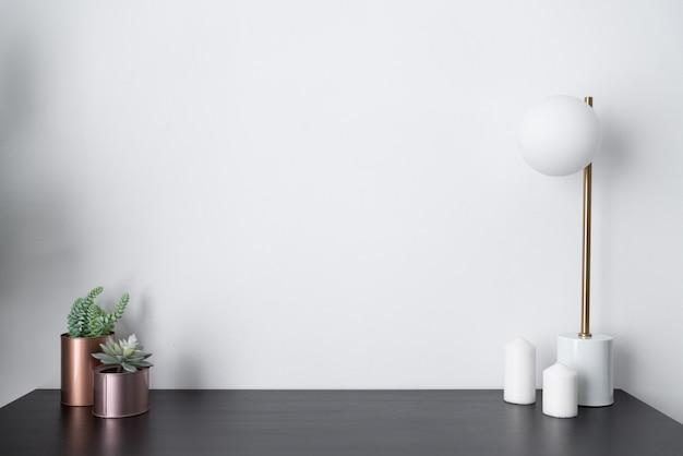 Composition de vase en cuivre de plantes artificielles et lampe de table élégante en or au milieu du siècle design moderne debout sur un plateau en bois noir avec du blanc
