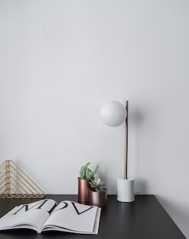 Composition de vase en cuivre de plantes artificielles et lampe de table en or debout sur un plateau en bois noir