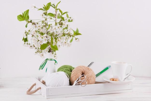 Composition avec un vase et un plateau en bois et des pelotes de laine pour travaux d'aiguille.