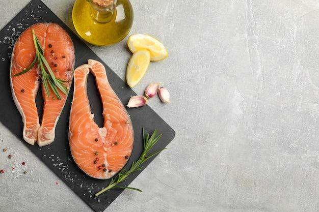 Composition avec viande de saumon et épices sur fond gris, vue de dessus