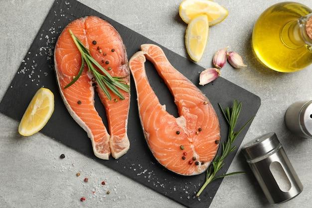 Composition avec viande de saumon et épices sur table grise, vue du dessus
