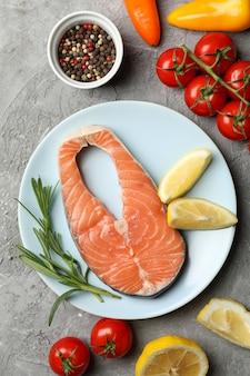 Composition avec viande de saumon et ingrédients sur table grise, vue de dessus