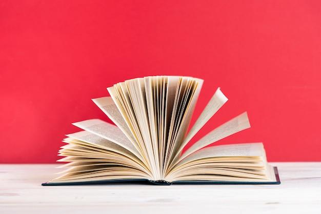 Composition avec vintage vieux livre cartonné, journal intime, pages ventilées sur table de terrasse en bois. retour à l'école. éducation