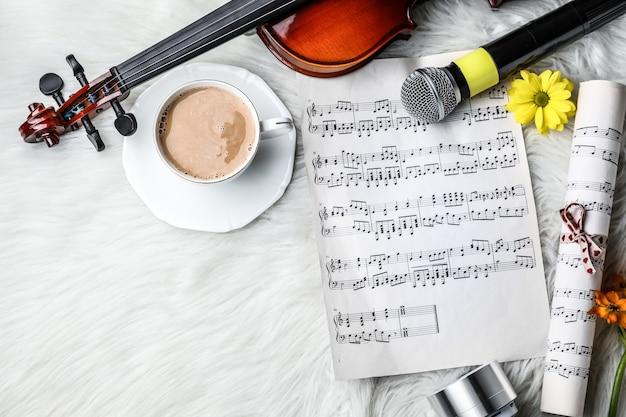 Composition avec violon, tasse de café et feuilles de musique sur plaid moelleux