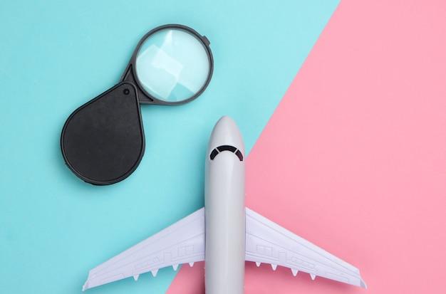 Composition de voyage à plat. figurine d'avion et loupe sur pastel bleu rose.