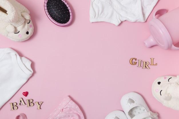 Composition vue de dessus avec accessoires pour bébés et vêtements sur une surface rose colorée