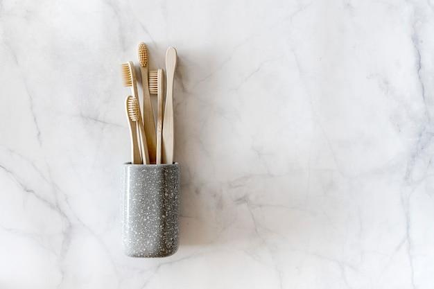 Composition vue de dessus avec brosses à dents en bambou biodégradables dans un pot gris sur fond de marbre