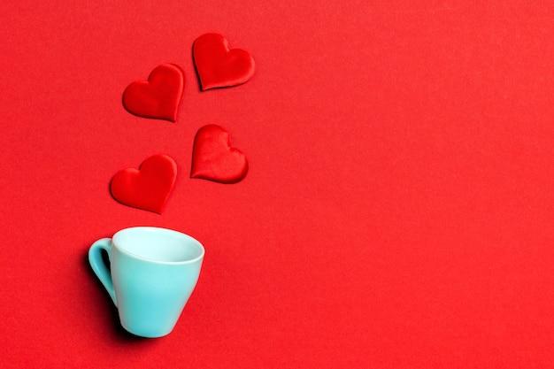 Composition vue de dessus des coeurs rouges tombant d'une tasse