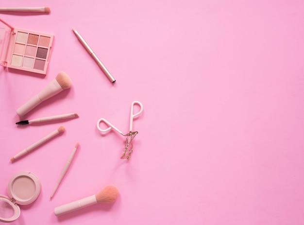 Composition de la vue de dessus définie pour le maquillage professionnel sur fond rose.