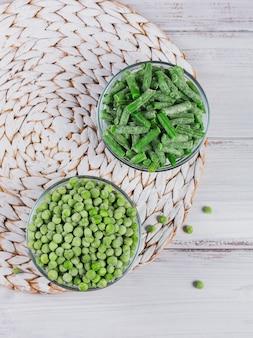 Composition vue de dessus avec différents légumes surgelés biologiques sur fond de bois blanc
