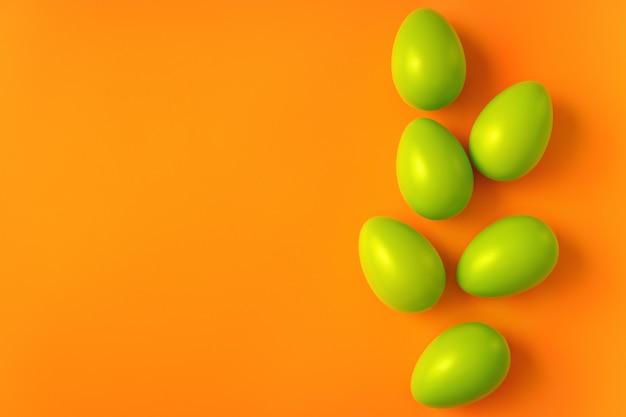 Compositon simple avec des oeufs de pâques verts sur fond orange vif